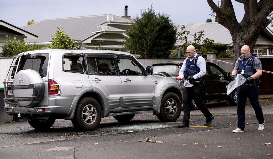 """In this March 27, 2019 photo, police walk past a vehicle where a man has died of stab wounds after a protracted standoff with armed police in Christchurch, New Zealand. A man who apparently killed himself during a standoff with police had posed a """"significant threat"""" to the community and supported the actions of the man who killed 50 Muslims at two mosques last month, New Zealand police said Wednesday, April 3, 2019. (Dean PurcellNew Zealand Herald via AP)"""