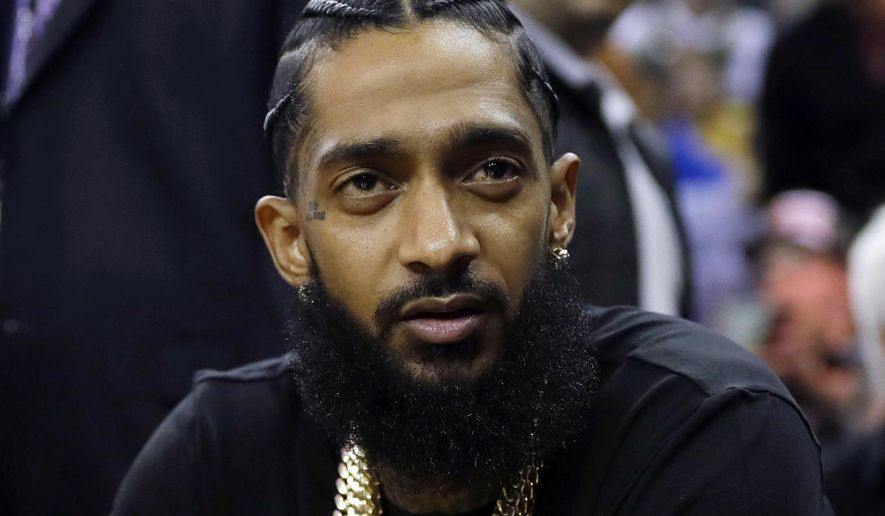 FILE - This March 29, 2018 file photo shows rapper Nipsey Hussle at an NBA basketball game between the Golden State Warriors and the Milwaukee Bucks in Oakland, Calif. Hussle was shot and killed Sunday, March 31, 2019 outside of his clothing store in Los Angeles. (AP Photo/Marcio Jose Sanchez, File)