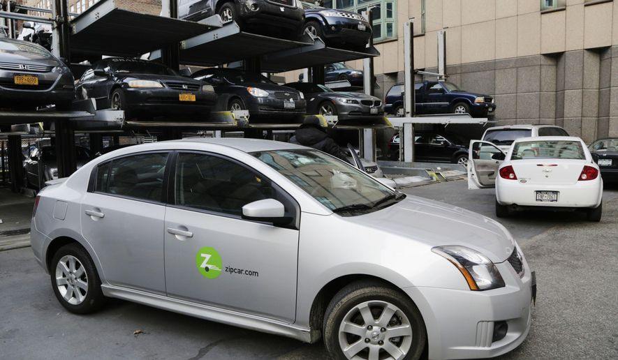 FILE- In this Jan. 2, 2013, file photo a Zipcar is parked at a lot in New York. Companies such as Zipcar and car2go eliminate the need to stand in line at rental car counters while waiting for vehicles, instead using smartphone apps to connect drivers with cars in their neighborhoods or nearby. (AP Photo/Mark Lennihan, File)