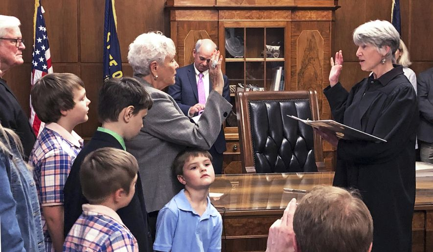 New Oregon Secretary of State Bev Clarno, left, surrounded by members of her extended family, including her great-grandson Logan Housden, age 6, center, is sworn in by Oregon Supreme Court Chief Justice Martha Walters during a ceremony at the Capitol in Salem Wednesday, April 3, 2019. The swearing in of Oregon's secretary of state marks the first time that women have held four of five statewide offices in the state. Just having turned 83, Clarno is also the oldest person to have ever held the office. (AP Photo/Andrew Selsky)