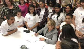New Mexico Gov. Michelle Lujan Grisham, seated, with pen, signs legislation to raise teacher salaries and increase annual spending on public schools by almost a half-billion dollars on Wednesday, April 3, 2019, at Salazar Elementary School in Santa Fe, N.M. State lawmakers are contending with a court order to increase funding for at-risk students. New Mexico is one of several states where parents have turned to the judiciary to address frustrations over state budget priorities and the quality of education. (AP Photo/Morgan Lee)