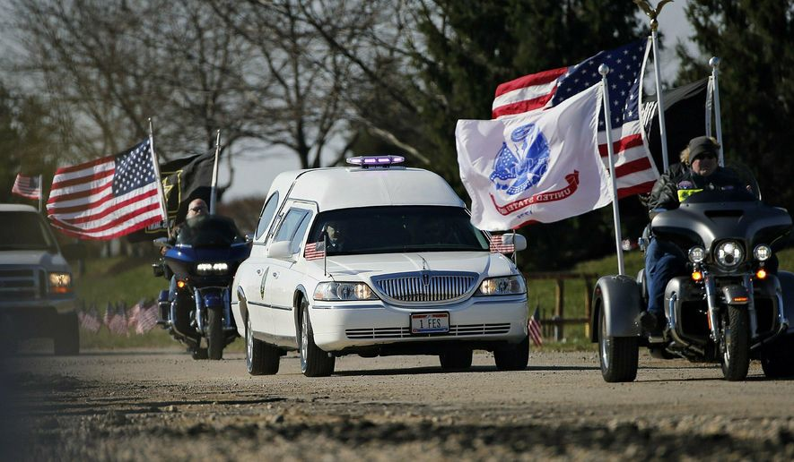 A hearse carrying the body of Army Spc. Joseph Collette, who died in combat in Afghanistan, heads to Lancaster at the start of the procession at Rickenbaker Air National Base in Columbus, Ohio on Wednesday, April 3, 2019. (Kyle Robertson/The Columbus Dispatch via AP)