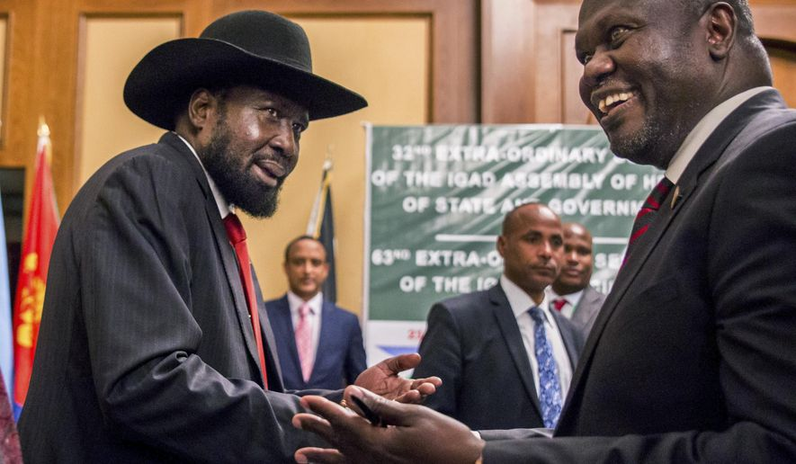 FILE - In this Thursday, June 21, 2018 file photo, South Sudan's President Salva Kiir, left, and opposition leader Riek Machar shake hands during peace talks in Addis Ababa, Ethiopia. South Sudan's committee overseeing the fragile transition from civil war has approved almost $185 million in spending on vehicles, food and home renovations while the country's peace deal suffers from an alleged lack of funds, according to internal documents seen by The Associated Press. (AP Photo/Mulugeta Ayene, File)