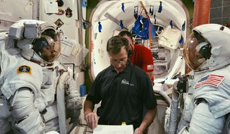 In this February 2019 photo made available by NASA and Boeing, Boeing astronaut Chris Ferguson helps NASA astronauts Nicole Mann, left, and Mike Fincke, right, train for a spacewalk inside the International Space Station Airlock Mockup at NASA's Johnson Space Center in Houston. The three are assigned to Boeing's Crew Flight Test, Starliner's first flight with crew as part of NASA's Commercial Crew Program. The Starliner capsule, supposed to make its debut in April 2019, was pushed back until August. (NASA/Boeing via AP)