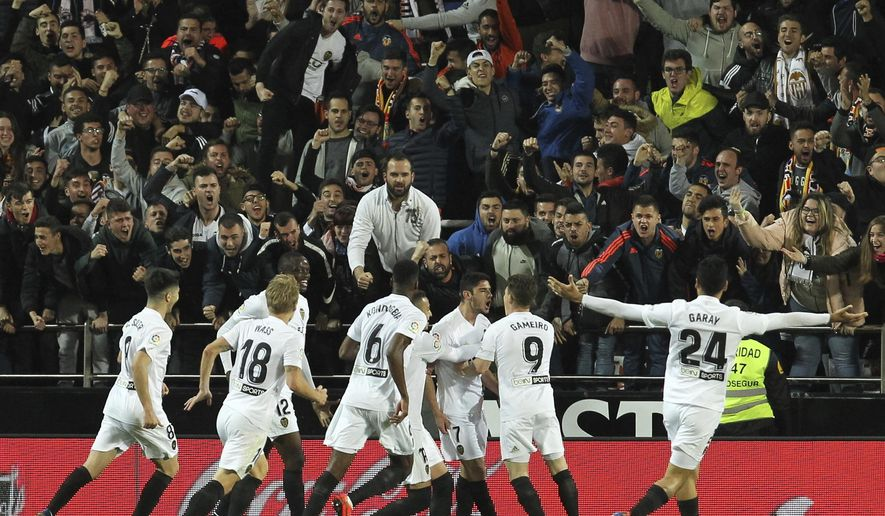 Valencia's Goncalo Guedes, center, celebrates with his teammate after scoring his opening goal during the Spanish La Liga soccer match between Valencia and Real Madrid at the Mestalla Stadium in Valencia, Spain, Wednesday, April 3, 2019. (AP Photo/Alberto Saiz)