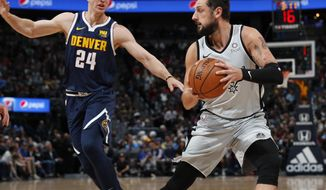 San Antonio Spurs guard Marco Belinelli, right, goes up for a basket as Denver Nuggets forward Mason Plumlee defends in the first half of an NBA basketball game Wednesday, April 3, 2019, in Denver. (AP Photo/David Zalubowski)
