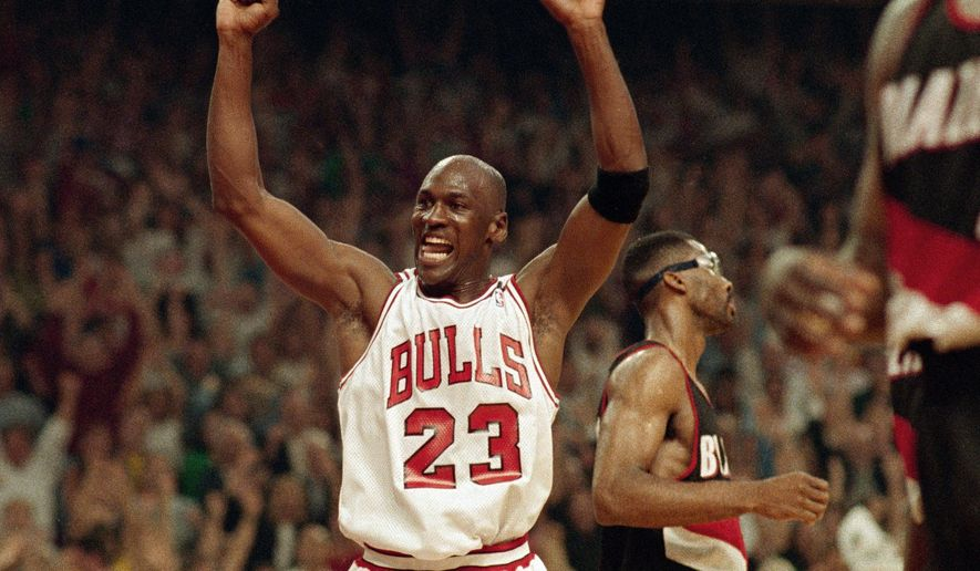 FILE - In this June 14, 1992, file photo, Michael Jordan celebrates the Bulls win over the Portland Trail Blazers in the NBA Finals in Chicago. Decades after Jordan's groundbreaking departure from college, March Madness and the NBA's mega-millions have taken all the novelty out of leaving early for the pros. (AP Photo/John Swart, File)