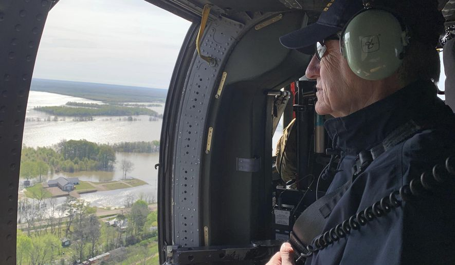 In this photo provided by the Mississippi Emergency Management Agency, Gov. Phil Bryant looks out at the backwater flooding surrounding the Valley Park community and neighboring farmland in Issaquena County, Miss. during a Wednesday, April 3, 2019 flyover by state and federal officials. (Ray Coleman/Mississippi Emergency Management Agency via AP)