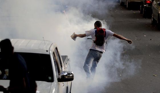 A man kicks away a tear gas canister launched by an unknown person near the site where supporters are waiting for Venezuelan opposition leader and self-proclaimed interim president Juan Guaido to speak, in Caracas, Venezuela, Monday, April 1, 2019. Officials loyal to Nicolas Maduro have said that Guaido is under investigation for inciting violence against the government and receiving illicit funds. (AP Photo/Natacha Pisarenko) **FILE**