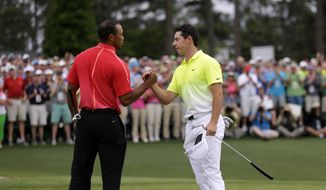 FILE - In this April 12, 2015, file photo, Tiger Woods, left, shakes hands with Rory McIlroy, of Northern Ireland, on the 18th hole during the fourth round of the Masters golf tournament, in Augusta, Ga. Woods hasn't won the Masters in 14 years. McIlroy needs to win it once to complete the Grand Slam.(AP Photo/David J. Phillip, File) **FILE**