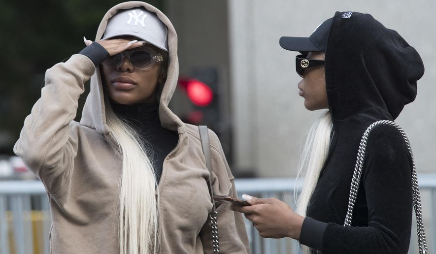 FILE - This July 11, 2018 file photo shows Shannade Clermont, left, and her twin sister Shannon outside of federal court in New York after her arraignment on charges she stole debit card information from a man who died from a drug overdose in his Manhattan apartment the morning after hiring her as a prostitute in 2017. Shannade Clermont was sentenced to a year in prison on Thursday, April 4, 2019. (AP Photo/Mary Altaffer, File)
