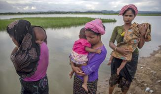 In this Oct. 18, 2017, file photo, Rohingya Muslim women, who crossed over from Myanmar into Bangladesh, stand holding their sick children after Bangladesh border guard soldiers refused to let them journey toward a hospital and turned them back toward the zero line border in Palong Khali, Bangladesh. (AP Photo/Dar Yasin, File)
