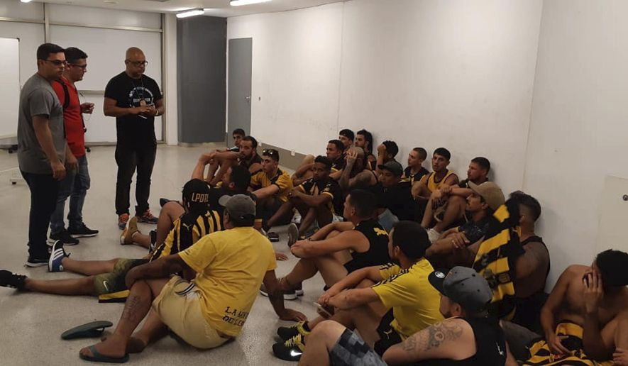BEST QUALITY AVAILABLE - Soccer fans of Uruguay's Penarol sit on the floor after being detained, at a special criminal Court for fans located at Maracana stadium in Rio de Janeiro, Brazil, Wednesday, April 3, 2019. Police detained close to 100 Penarol fans involved in a brawl with fans of Brazil's Flamengo, hours before the two were to meet in a game valid for the Copa Libertadores tournament. (AP Photo/Diarlei Rodriguez)