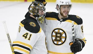 Boston Bruins goaltender Jaroslav Halak (41), of Slovakia, and Karson Kuhlman (83) celebrate a win against the Minnesota Wild after an NHL hockey game Thursday, April 4, 2019, in St. Paul, Minn. The Bruins won 3-0. (AP Photo/Hannah Foslien)