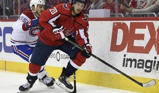 Washington Capitals Lars Eller (20), or Denmark, carries the puck under pressure from Montreal Canadiens Andrew Shaw (65) during the second period of their NHL hockey game in Washington, Thursday, April 4, 2019. (AP Photo/Susan Walsh)