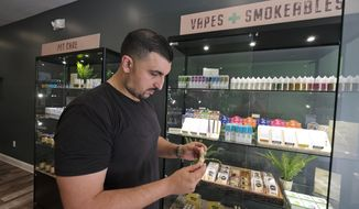 In this photo taken Thursday, March 21, 2019, Gus Dabais looks over CBD products he sells at his Sidewalk Wellness store in San Francisco. CBD oil-infused food, drinks and dietary supplements are popular even though the U.S. government says they're illegal and some local authorities have forced retailers to pull products. The confusion has California, Texas and other states moving to legalize the cannabis compound that many see as beneficial to their health. (AP Photo/Eric Risberg)