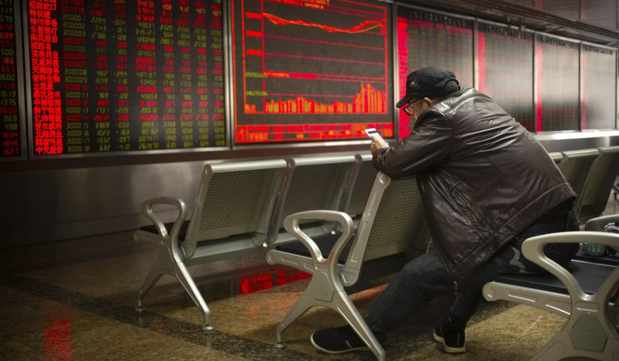 A Chinese investor uses his cellphone as he monitors stock prices at a brokerage house in Beijing, Thursday, April 4, 2019. Shares were mixed in Asia on Thursday after modest gains overnight on Wall Street.(AP Photo/Mark Schiefelbein)
