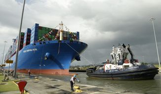 In this Dec. 3, 2018, file photo, a Panama Canal worker docks the Chinese container ship Cosco at the Panama Canals' Cocoli Locks, in Panama City. China's expansion in Latin America of its Belt and Road initiative to build ports and other trade-related facilities is stirring anxiety in Washington. As American officials express alarm at Beijing's ambitions in a U.S.-dominated region, China has launched a charm offensive, wooing Panamanian politicians, professionals, and journalists. (AP Photo/Arnulfo Franco)  **FILE**