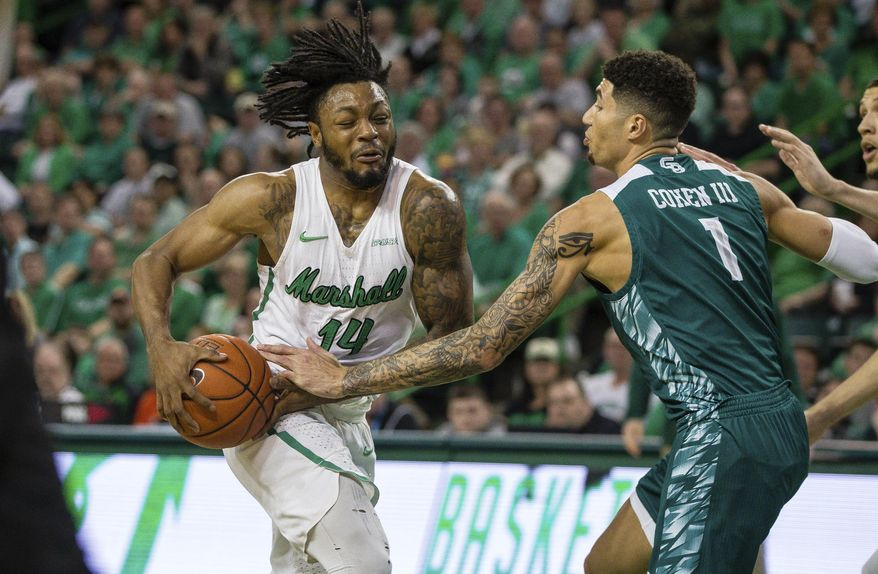 Marshall's C.J. Burks (14) drives the the basket against Green Bay's Sandy Cohen (1) in the championship game of the CollegeInsider.com Tournament on Thursday, April 4, 2019, at the Cam Henderson Center in Huntington, W.Va. (Sholten Singer/The Herald-Dispatch via AP)