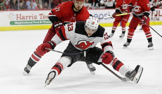 Carolina Hurricanes' Nino Niederreiter (21), of the Czech Republic, and New Jersey Devils' Nico Hischier (13), of Switzerland, chase the puck during the second period of an NHL hockey game in Raleigh, N.C., Thursday, April 4, 2019. (AP Photo/Gerry Broome)