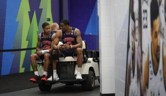 Auburn's Horace Spencer (0) and J'Von McCormick get a ride on a golf cart after a practice session for the semifinals of the Final Four NCAA college basketball tournament, Thursday, April 4, 2019, in Minneapolis. (AP Photo/David J. Phillip)