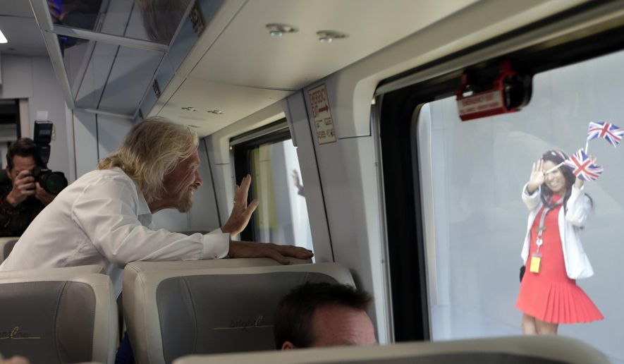 An employee holding British flags waves as Richard Branson, of Virgin Group, left, departs on a Brightline train bound for Miami, Thursday, April 4, 2019, in West Palm Beach, Fla. The state's Brightline passenger trains are being renamed Virgin Trains USA after Branson invested in the new fast-rail project that is scheduled to connect Miami with Orlando. (AP Photo/Lynne Sladky)