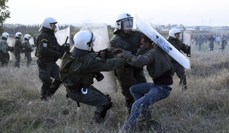 Riot police detain a protesting migrant during a rally outside a refugee camp in the village of Diavata, west of Thessaloniki, northern Greece, Thursday, April 4, 2019. Clashes broke out between migrants and Greek police outside a camp in northern Greece, where hundreds gathered following anonymous social media calls for a long trek through heavily guarded Balkan borders to seek asylum in Europe's prosperous heartland. (AP Photo/Giannis Papanikos)