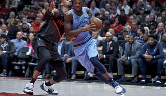 Memphis Grizzlies guard Delon Wright, right, drives past Portland Trail Blazers guard Rodney Hood during the first half of an NBA basketball game in Portland, Ore., Wednesday, April 3, 2019. (AP Photo/Craig Mitchelldyer)