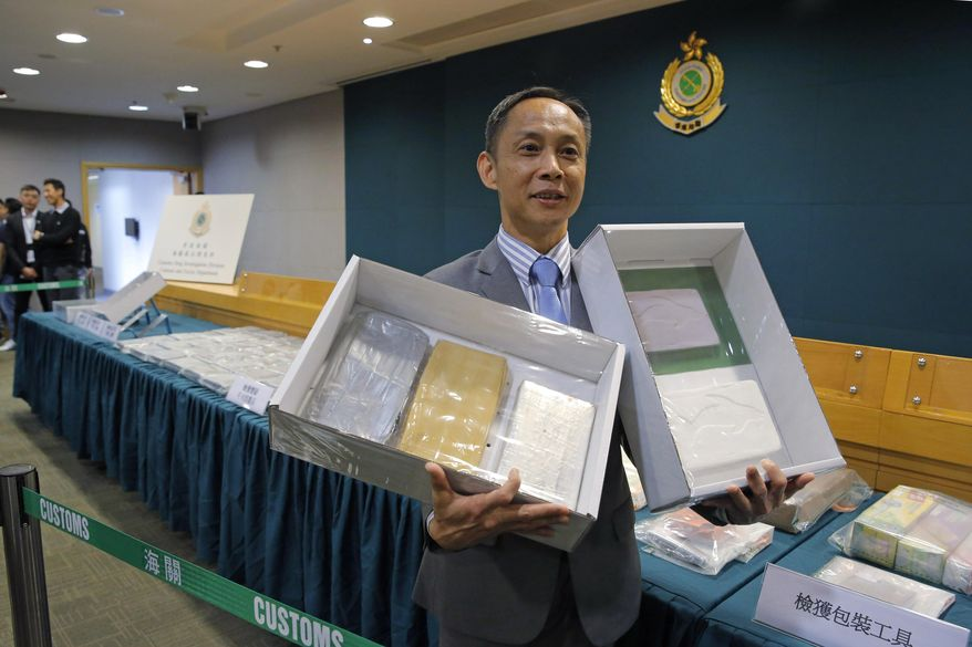 Head of Customs Drug Investigation Bureau Hui Wai-ming holds the seized cocaine during a news conference in Hong Kong, Thursday, April 4, 2019. A haul of cocaine with an estimated market value of $13 million has been seized in Hong Kong, customs agents said Thursday.(AP Photo/Kin Cheung)
