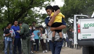 In this March 14, 2019, photo, Jose Fermin Gonzalez Cruz holds his son, William Josue Gonzales Garcia, 2, as they wait with other families who crossed the nearby U.S.-Mexico border near McAllen, Texas, for Border Patrol agents to check names and documents. A surge in family arrivals, largely from Guatemala and Honduras, has led Border Patrol agents to shift attention from preparing criminal cases to caring for children. (AP Photo/Eric Gay) **FILE**