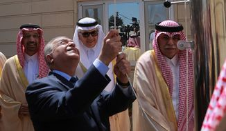 Iraq Foreign Minister Mohamed Alhakim raises the Saudi flag during the opening ceremony of the Saudi consulate in Baghdad, Iraq, Thursday, April 4, 2019. Saudi Arabia is opening four new consulates in Iraq and plans to invest one billion dollars for projects in Iraq. (AP Photo/Hadi Mizban)