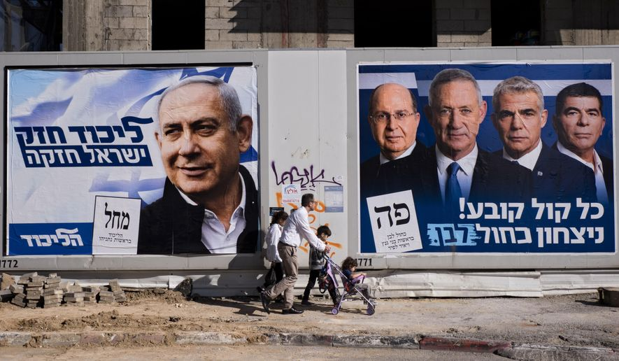 """People walk by election campaign billboards showing Israeli Prime Minister and head of the Likud party Benjamin Netanyahu, left, alongside the Blue and White party leaders, from left to right, Moshe Yaalon, Benny Gantz, Yair Lapid and Gabi Ashkenazi, in Tel Aviv, Israel, Wednesday, April 3, 2019. Hebrew on billboards reads, left """"Strong Likud strong Israel"""" on the right """"Every vote matters, win Blue and White"""". (AP Photo/Oded Balilty)"""