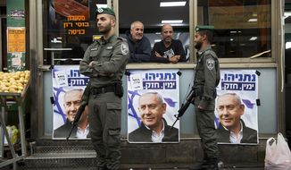 In this Tuesday, April 2, 2019, file photo, Israeli border police officers stand guard next to posters depicting Israeli Prime Minister Benjamin Netanyahu at the Ha'tikva market in Tel Aviv, Israel. As Israel prepares to hold a national election next week, experts say it is vulnerable to the kind of foreign hacks and cyber campaigns that have disrupted the political process in other countries. (AP Photo/Oded Balilty, File)