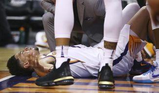 An injured Phoenix Suns guard Devin Booker pauses on the floor after turning his ankle during the first half of the team's NBA basketball against the Utah Jazz Wednesday, April 3, 2019, in Phoenix. Booker left the game. (AP Photo/Ross D. Franklin)