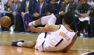 An injured Phoenix Suns guard Devin Booker reaches for his ankle after turning it during the first half of the team's NBA basketball against the Utah Jazz on Wednesday, April 3, 2019, in Phoenix. (AP Photo/Ross D. Franklin)