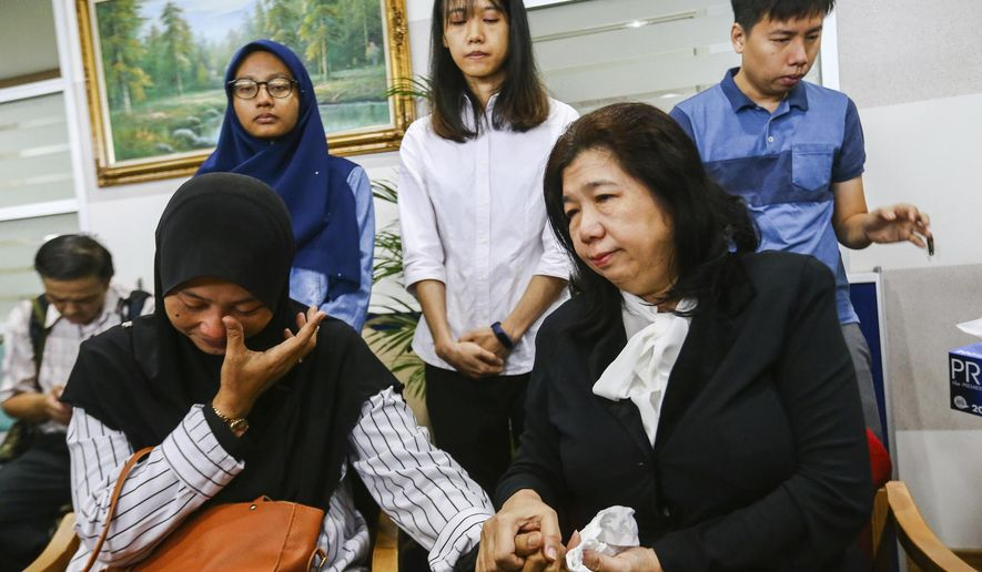 In this photo taken Wednesday, April 3, 2019, Norhayati Mohd Arifin, sitting at left, wife of Amri Che Mat and Susanna Liew Sow Yoke,  sitting at right, wife of Pastor Raymond Koh react during the announce the findings of the Public Inquiry into the disappearances of Pastor Raymond Koh and Amri Che Mat at National Human Rights Commission office in Kuala Lumpur, Malaysia. Malaysia's government was urged Thursday to reinvestigate the disappearances of a Christian pastor and a Muslim activist after a public inquiry concluded the duo were abducted by the police special branch over matters against Islam. (AP Photo)