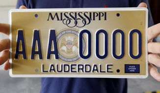 """FILE - In a Thursday, May 10, 2018 file photo, Clay Chandler, director of communications for Gov. Phil Bryant, holds Mississippi's new standard license plate at the Capitol in Jackson, Miss. It will display the state seal that includes the phrase, """"In God We Trust."""" The American Humanist Association, a national group that includes atheists and agnostics is objecting to Mississippi's new standard license plate design that has the phrase """"In God We Trust."""" (AP Photo/Rogelio V. Solis, Filw)"""