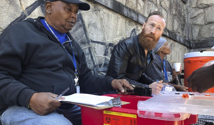 In this March 20, 2019 photo, Harry Ethridge, client services manager at the Atlanta Harm Reduction Coalition, and Jonathan Spuhler, an outreach coordinator for Absolute Care and volunteer at AHRC, set up a needle exchange station for drug users to swap out used syringes for clean syringes on English Avenue, in Atlanta. (AP Photo/Sanya Mansoor)