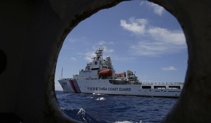 """In this photo taken March 29, 2014, a Chinese Coast Guard ship attempts to block a Philippine government vessel as the latter tries to enter Second Thomas Shoal to relieve Philippine troops and resupply provisions. The Philippine government publicly protested on Thursday the swarming of Chinese flotillas near islands and islets occupied by Filipinos in the disputed South China Sea as illegal and vowed to continue confronting such actions by China's fishermen or military with """"appropriate action."""" (AP Photo/Bullit Marquez, File)"""