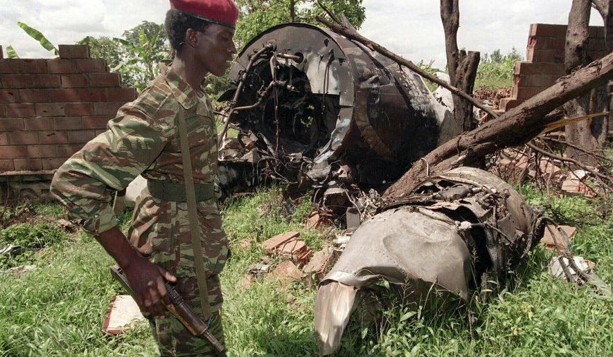FILE - In this May 23, 1994, file photo, a Rwandan Patriotic Front (RPF) rebel walks by the plane wreckage in which Rwanda's President Juvenal Habyarimana died April 6, 1994, in Kigali, Rwanda. Twenty-five years ago Rwanda descended into violence in which some 800,000 Tutsis and moderate Hutus were massacred by the majority Hutu population over a 100-day period in what was the worst genocide in recent history. (AP Photo/Jean-Marc Boujou, File)