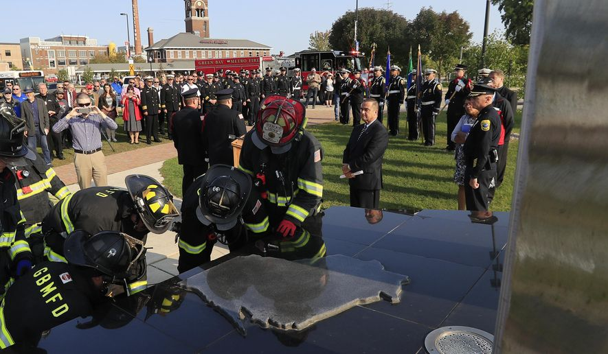 In a Monday, September 11, 2017 photo, Green Bay firefighters remove parts of the Sept. 11 memorial at its decommissioning ceremony in Green Bay, Wis. City Council members voted unanimously in August to remove the memorial due to its deterioration and inaccuracies information on it, after fundraising efforts to repair it failed to generate even a dime. (Adam Wesley/The Post-Crescent via AP)