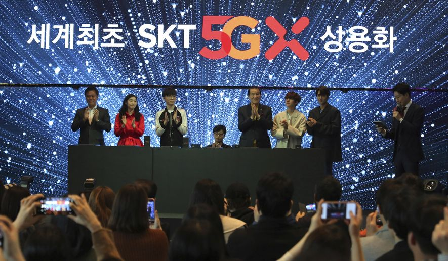 "SK Telecom CEO Park Jung-ho, left, and participants attend a media showcase for its 5G service in Seoul, South Korea, Wednesday, April 3, 2019. SK Telecom will be launching commercial 5G services nationwide on Friday, April 5, in line with its competitors. The signs read: ""The world's first commercial services."" (AP Photo/Ahn Young-joon)"