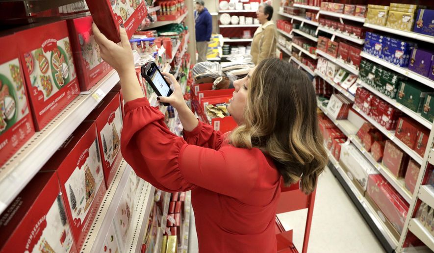 FILE- In this Nov. 16, 2018, file photo Target employee Lindsay Walker scans an item as she collects merchandise from shelves to prep them for an online order at a Target store in Edison, N.J. Target is raising the minimum hourly wage for its workers for the third time in less than two years. The discounter said Thursday, April 4, 2019, that it plans to raise the hourly starting wage to $13 from $12 in June. (AP Photo/Julio Cortez, File)