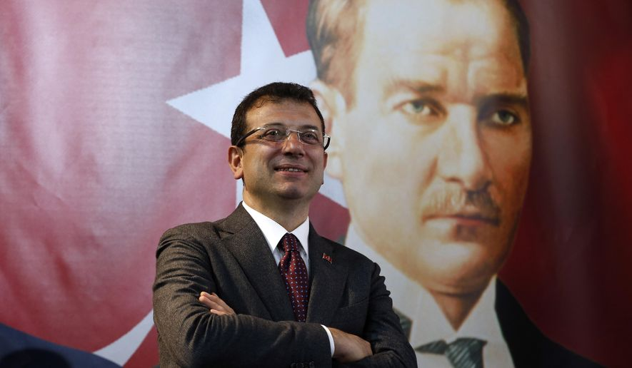 Backdropped by a poster of modern Turkey's founder Mustafa Kemal Ataturk, right, Ekrem Imamoglu, the opposition, Republican People's Party's (CHP) mayoral candidate in Istanbul, poses for The Associated Press following an interview in Istanbul, Thursday, April 4, 2019. Imamoglu said he's confident that the result of a recount of votes in the city will confirm his victory and has renewed an appeal to Turkey's President Recep Tayyip Erdogan to help end the standoff. Imamoglu won the tight race for Istanbul in Sunday's local elections in a major upset for Erdogan, who rose to power as the mayor of the city of 15 million and has said that whoever wins Istanbul wins to whole of Turkey. (AP Photo/Lefteris Pitarakis)