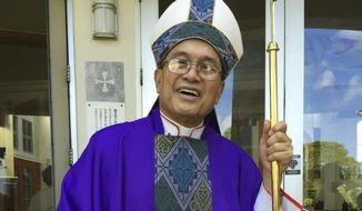 FILE - In this Nov. 30, 2014 file photo, Archbishop Anthony Apuron stands in front of the Dulce Nombre de Maria Cathedral Basilica in Hagatna, Guam. On Thursday, April 4, 2019 the Vatican upheld its conviction of Guam's ousted archbishop Apuron for sexually abusing minors and has added a further penalty on appeal that effectively prevents him from presenting himself as a bishop. (AP Photo/Grace Garces Bordallo, File)
