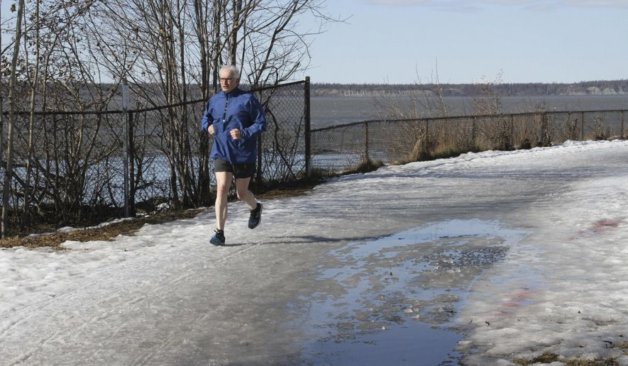 This April 3, 2019, photo shows a man wearing shorts running on the coastal trail in Anchorage, Alaska. Much of Anchorage's snow disappeared as Alaska experienced unseasonably warm weather in March. (AP Photo/Mark Thiessen)