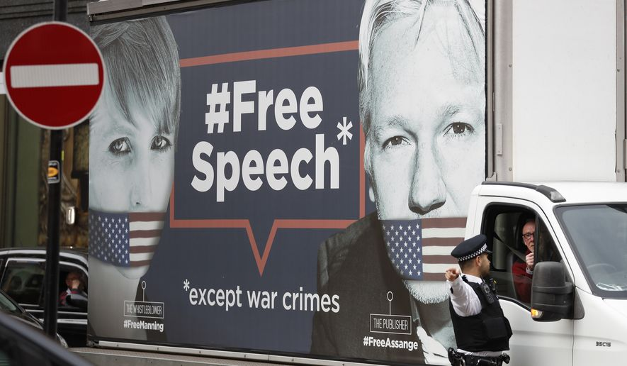 A policeman directs a van with a 'Free Speech' placard and the images of Wikileaks founder Julian Assange and whistleblower Chelsea Manning on its side, near the Ecuadorian Embassy, in London, Friday, April 5, 2019. (AP Photo/Alastair Grant)