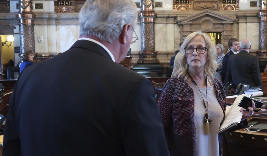 Kansas state Sen. Mary Pilcher-Cook, right, R-Shawnee, confers with Senate health committee Chairman Gene Suellentrop, R-Wichita, before a vote on an anti-abortion bill that they both support, Friday, April 5, 2019, at the Statehouse in Topeka, Kansas. The bill requires abortion providers to tell women using medication to end their pregnancies that the process can be reversed after they take the first of two pills. (AP Photo/John Hanna)