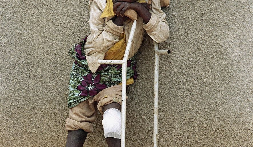 FILE - In this Friday May 13, 1994 file photo a boy who survived a massacre at the Rwandan village of Karubamba rests on his crutches on at a hospital in nearby Gahini, Rwanda. The boy's leg was injured by a machete during the April massacre in Karubamba. Nobody lives here anymore. Not the expectant mothers huddled outside the maternity clinic, not the families squeezed into the church, not the man who lies rotting in a schoolroom beneath a chalkboard map of Africa. (AP Photo/Jean-Marc Bouju, File)
