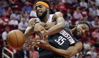New York Knicks center Mitchell Robinson and Houston Rockets forward Kenneth Faried (35) both lose the ball on a rebound during the first half of an NBA basketball game Friday, April 5, 2019, in Houston. (AP Photo/Michael Wyke)
